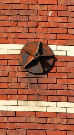oxidized: Old, star shape on circle, wall anchor rusts on exterior of historic building in downtown Houghton, Michigan.