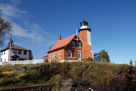 lake dwelling: Eagle Harbor Lighthouse and visitor center sit on cliff overlooking Lake Superior in Upper Peninsula, Michigan.  Lighthouse is brick architecture and Visitor Center is white frame.