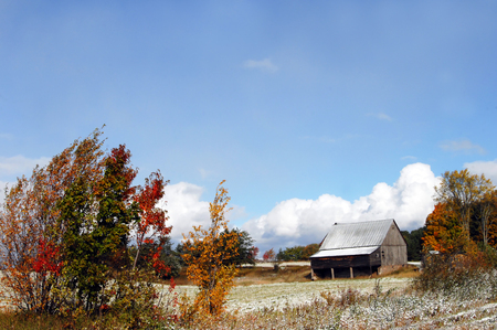 michigan snow: This Michigan farm in Autumn has both snow and colorful foliage.  Blue sky and clouds add to the colorful landscape.