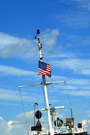 portage: Army Corps of Engineers, tub boat, flies American flag.  Blue sky frames metal mast.  Tug boat is docked in Portage Lake next to Houghton Michigan.