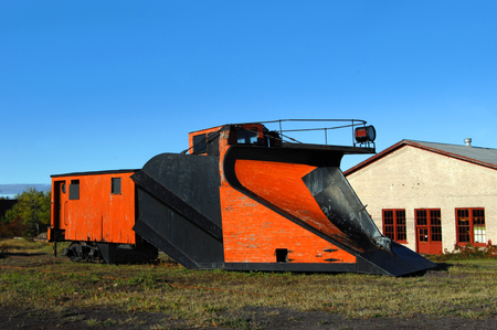 snow plow: Vintage railroad car sits besides abandoned railroad track in Upper Penninsula, Michigan.  Railroad car has front-mounted plow for snow removal on tracks.