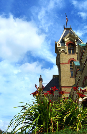 lintels: Victorian era, Houghton County Courthouse in Houghton, Michigan is designed with local red sandstone and Lake Superior copper for the roof.  Red lillies bloom in foreground. Stock Photo