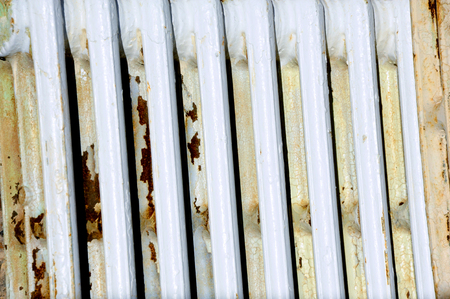 Antique heater rusts outdoors exposed to elements.  Background images shows rows of white metal.