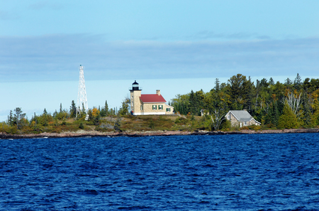 choppy: Automated light and historic Copper Harbor Lighthouse is visited by tourists.  Choppy waters of Lake Superior is deep blue and Fall colors shoreline.