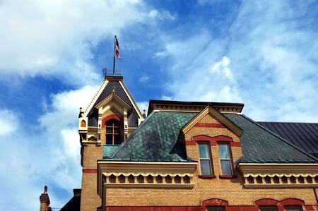 lintels: Elegant victorian architecture graces the Houghton County Courthouse.  Red sandstone accents window arches and copper clads roof.  American flag flies in blue skies over city of Houghton, Michigan.
