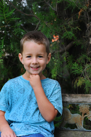 leans on hand: Little boy gives a stock grin and leans his chin on his hand.  He is posing outdoors with trees as his background and a wooden bench to sit on.  His shirt is blue.
