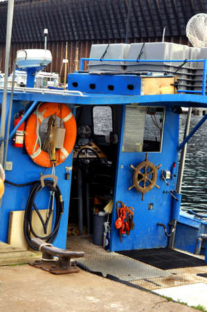 Small fishing boat sits docked at the harbor in Marquette, Michigan.  Bright blue paint covers cabin and deck.  Old vintage nautical wheel hangs besides boat control.