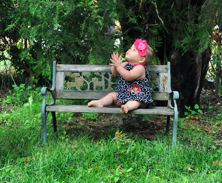 Baby girl sits on wooden park bench and folds her hands to pray.  Her eyes are lifted heavenward.
