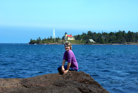 Attractive woman poses on the rocky shoreline of Lake Superior.  In the background is the Copper Harbor Lighthouse and Lighthouse Keepers House.