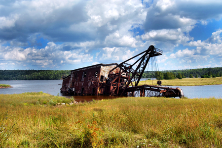 relic: A relic of the copper industry in Upper Penninsula, Michigan, lays rusting in Torch Lake.  Stormy clouds hover overhead. Stock Photo