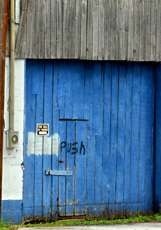 padlocked: Old, bright blue, wooden building was once used for business and is now closed and padlocked.  The word push is hand painted on the doorway next to a for sale by owner sign. Stock Photo