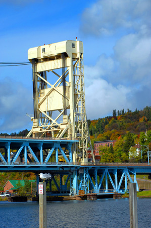 portage: Tall tower of the Portage Lake Lift Bridge, connecting Houghton and Hancock, Michigan,  is painted white and drawbridge is painted blue.  Seagull sits on post of pier and autumn colors landscape.