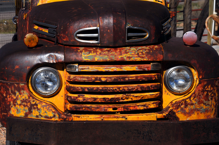 rusts: Vintage Ford truck rusts as it is exposed to the elements.  Yellow paint has almost peeled completely off.