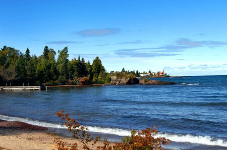 lake fronts: Wooden pier fronts image; rustic and weathered on Lake Superior, Michigan.  Background shows Eagle Harbor Lighthouse and Keweenaw Peninsula. Stock Photo