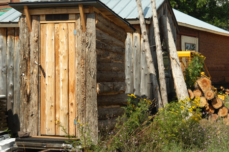 outhouse: Rustic log sided, outhouse sits for sale in Upper Peninsula, Michigan.