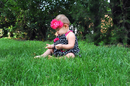Baby girl holds blade of grass and examines it.  She is sitting in the grass with barefeet. Imagens