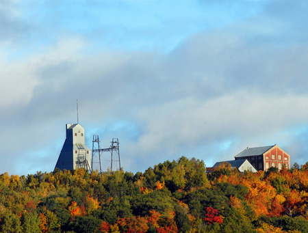 industry park: Quincy Hill is covered in Autumn color.  Quincy Shaft and the Keweenaw National Historical Park sit topping Quincy Hill surrounded by Fall foliage.  Historical park preserves remains of the copper mining industry.