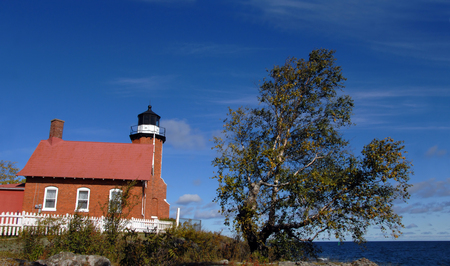 lake michigan lighthouse: Eagle Harbor Lighthouse stands guard over Lake Superior in Upper Peninsula, Michigan.  Brick architecture with black domed light has keepers home attached to lighthouse.