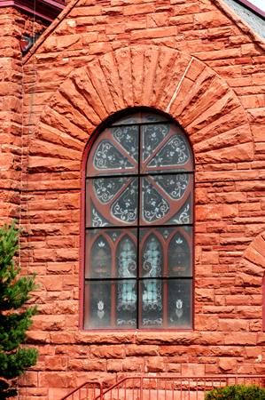 methodist: Arched stained glass window is framed by Jacobsville sandstone on the Grace United Methodist Church in Houghton, Michigan. Stock Photo