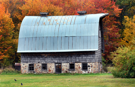round brilliant: Dutch influenced country barn has round tin roof, shingle siding and stone foundation.  Brilliant Autumn leaves surround barn.
