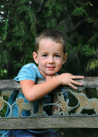 day dreams: Little boy enjoys his boyish day dreams as he leans against a wooden bench in wooded park.  He has on a blue shirt and jeans.