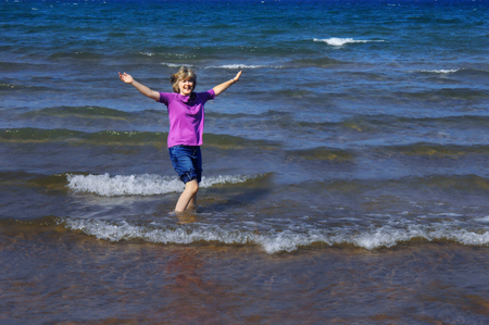 wide  wet: Older woman, revisits her childhood, rolls up her jeans and gets wet in Lake Superior in Upper Peninsula, Michigan.  She is smiling and laughing and her arms are thrown wide. Stock Photo