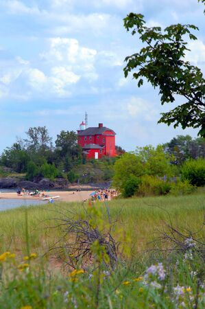 marquette: Beach goers are treated in scenic view of the Marquette Maritime Museum and Lighthouse as it sits atop bluff overlooking shoreline.  Building is red and is three stories in height.