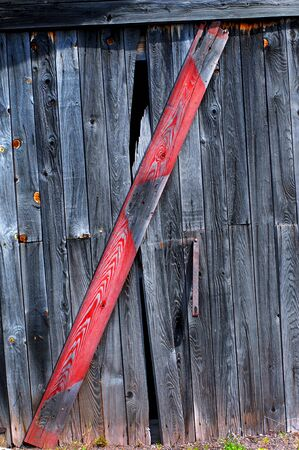 boarded up: Broken board on old, weathered grey barn is boarded up with a colorful red plank. Stock Photo