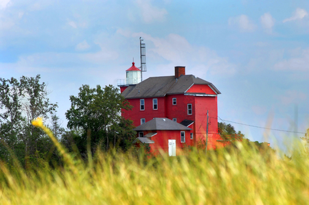 Tall grass frames the Marquette Maritime Museum and Lighthouse in Marquette, Michigan.  Building is red, wooden and sits atop a wooden bluff overlooking Lake Superior.