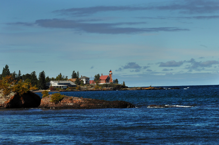 lake dwelling: Darkness approaches and the Eagle Harbor Lighthouse sends out its beam of light to warn approaching ships of the rocky shoreline.  Lighthouse is on Lake Superior on the Keweenaw Peninsula, Michigan. Stock Photo