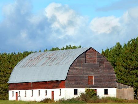풍화 붉은 나무와 소박한 헛간 깡통 지붕 및 블록 자료있다. 헛간은 Keweenaw 반도의 어퍼 반도, 미시간에 위치하고 있습니다.