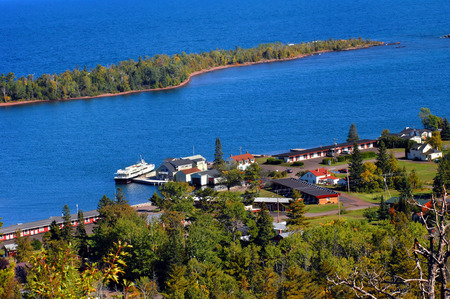 boat dock: Brockway Mountain Drive overlooks the Isle Royal boat dock and surrounding buildings.  Vivid blue waters of Copper Harbor and Lake Superior fill image. Stock Photo