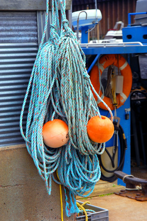 coiled rope: Coiled rope and floats hang on pier next to bright blue fishing boat.