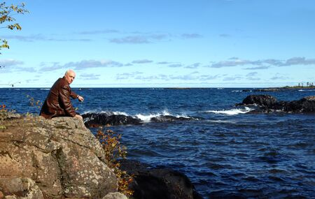 upper peninsula: Retired man sits on Lake Superiors rocky shoreline in Upper Peninsula, Michigan.  He is sitting on a rocky cliff overlooking the deep blue water.  Cold Fall weather makes his coat a necessity. Stock Photo