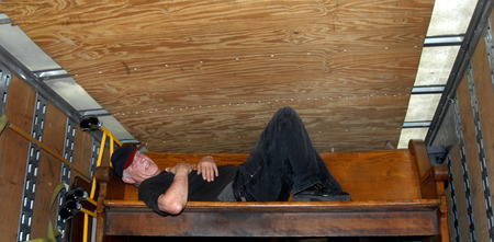 moving van: Mature man collapses on an old church pew that he is moving out of a moving van.  His face is covered with sweat and he is laying full length on the old wooden pew. Stock Photo