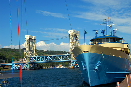 royale: The MV Ranger III sits at dock at the city of Houghton, Michigan.  Ship belongs to the National Park Service and provides transportation to Isle Royale National Park.  Portage Lake Lift Bridge sits in background. Stock Photo