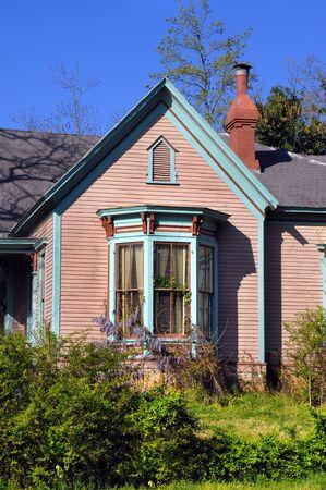 case colorate: casa vittoriana è decorato con finiture in legno verde e marrone. Bay finestra ha Wysteria viola cresce su di esso. Archivio Fotografico