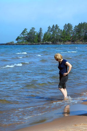 Woman rolls up her jeans and wades in the cool waters of Lake Superior in Upper Peninsula Michigan.