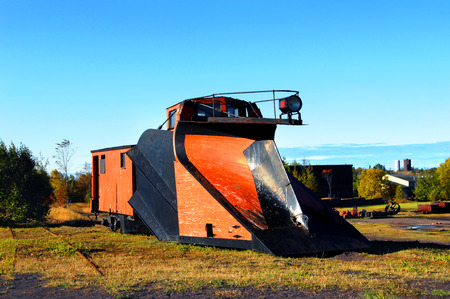 wood railroads: Vintage railroad car sits besides abandoned railroad track in Upper Penninsula, Michigan.  Railroad car has front-mounted plow for snow removal on tracks.