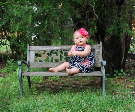 hair bow: Little girl sits on wooden park bench.  She is wearing a summer frock in black and white.  Her hair has a pink flower hair bow.  Her thoughts are quiet and peaceful.