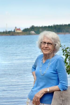 leaning on elbows: Older woman stands besides Lake Superior with view of lighthouse in background.  Her shirt is soft blue and she is wearing a silver neclace. Stock Photo