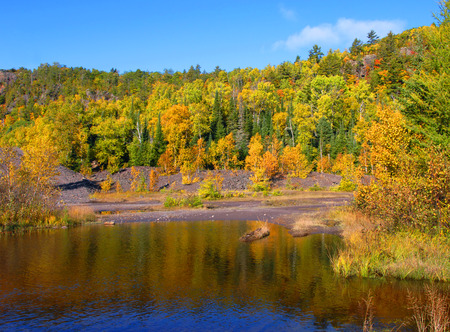 wastes: Autumn reflects in the pools and mining wastes from Cliff Mine in Upper Penninsula, Michigan.  Copper Mine operated in the Michigan copper district from 1845 to 1887. Stock Photo