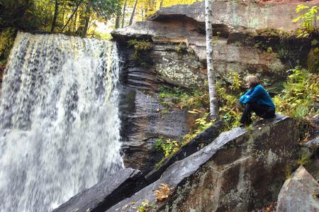 large rock: Adult female sits on large rock besides Hungarian Falls in Upper Peninsula, Michigan.