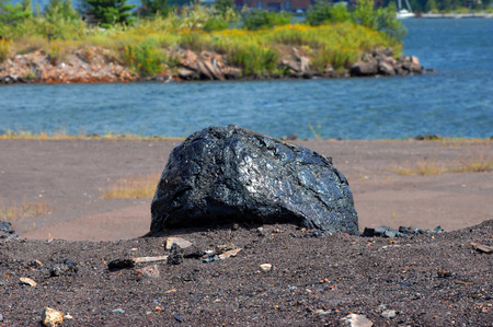 slag: Copper slag rock sits on shore of Portage Lake near Hancock, Michigan.  Large black rock shines in the sun. Stock Photo