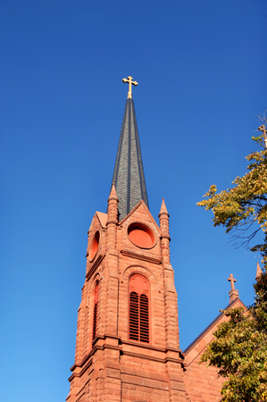 upper peninsula: Cross topped steeple of the St. Paul the Apostle Church in Calumet, Michigan, is framed by vivd blue skies.  Church is constructed on red sandstone quaried in the Upper Peninsula. Stock Photo