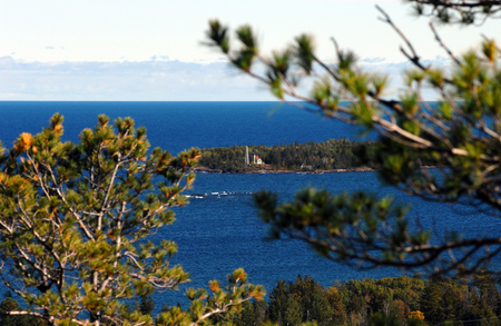 scenic drive: Surrounded by Lake Superior and Copper Harbor, the Copper Harbor Lighthouse is framed by trees on the Brockway Mountain scenic drive.