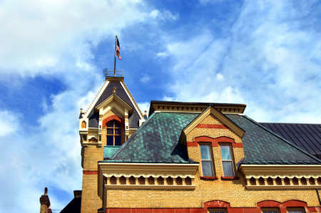 lintels: Courthouse in Houghton, Michigan is detailed with locally mined red sandstone.  Roofline is copper and is topped with American flag.