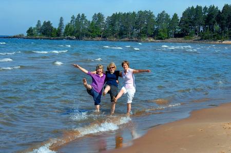 Drie zusters opnieuw hun jeugd en kick en plons in het water van Lake Superior in Upper Peninsula, Michigan. Ze lachen en schoppen tot hun hielen.