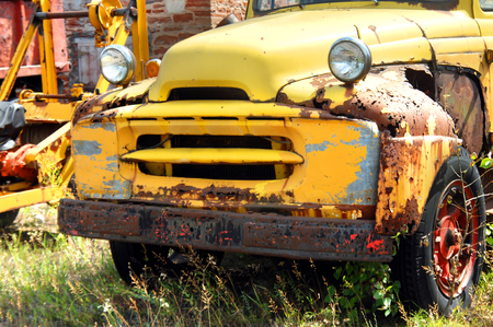 rusting: Old International Harvester pickup truck sits abandoned and rusting.  It has bright yellow paint that is peeling and cracked.