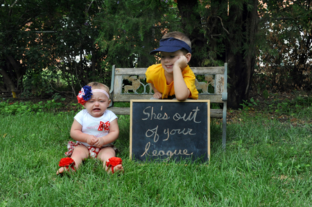 he   my sister: Baby sister sits besides sign stating she is out of your league.  Brother leans over sign smiling.  Sister is crying.  She is wearing a cheerleader uniform and he is wear a baseball uniform. Stock Photo